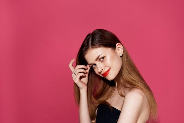 Femme en robe noire lèvres rouges glamour fond rose glamour. photo de haute qualité