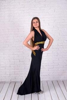 Femme en robe noire sur mur de briques blanches