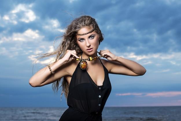 Femme en robe noire posant au bord de la mer