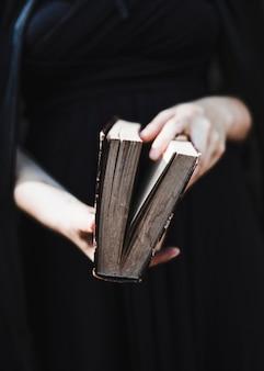 Femme en robe noire tenant un livre ancien