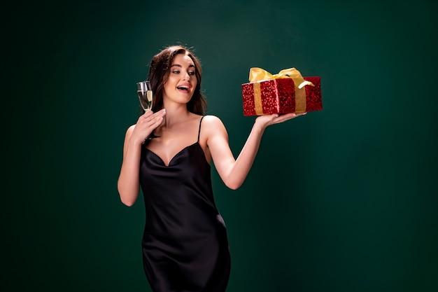 Femme En Robe Noire Tient La Boîte Rouge Cadeau Et Verre De Champagne Party Time Concept De Vacances Photo Premium