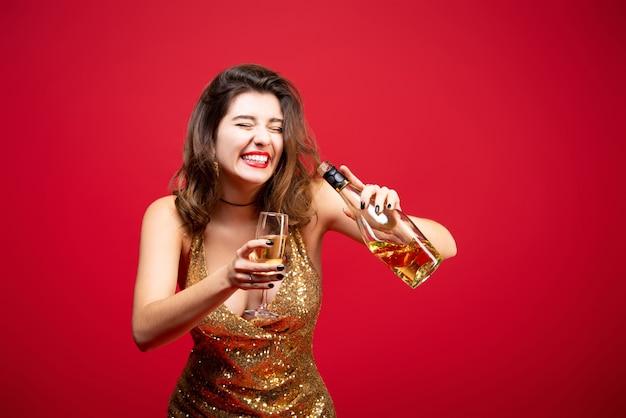 Femme en robe d'or avec rouge à lèvres et champagne à la main