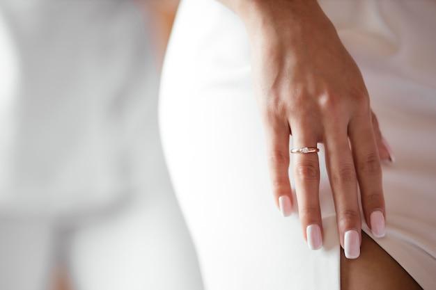Une femme en robe passe sa main le long de sa jambe