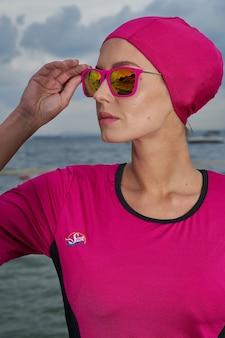Femme en robe rose et foulard rose et lunettes de soleil