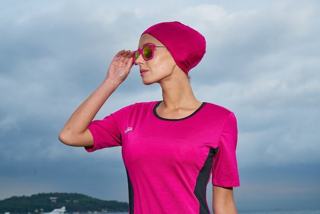 Femme en robe rose et foulard rose