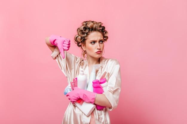 Femme en robe rose montre le doigt vers le bas et détient un détergent sur un mur isolé