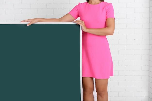 Femme en robe rose avec tableau noir vert contre le mur de briques, gros plan