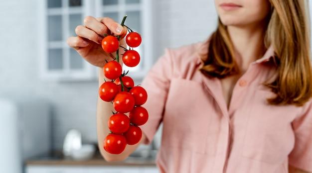Femme en robe rose tient une branche de tomates cerises mûres, gros plan