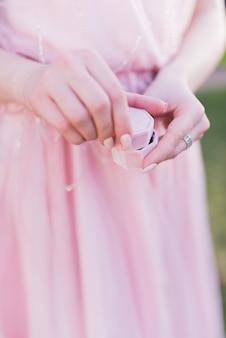 Femme en robe rose tient une petite boîte présente