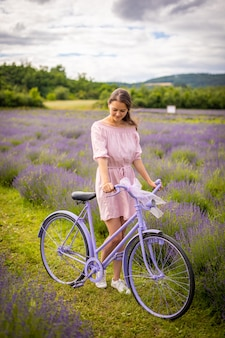 Femme en robe rose avec vélo rétro en république tchèque champ de lavande