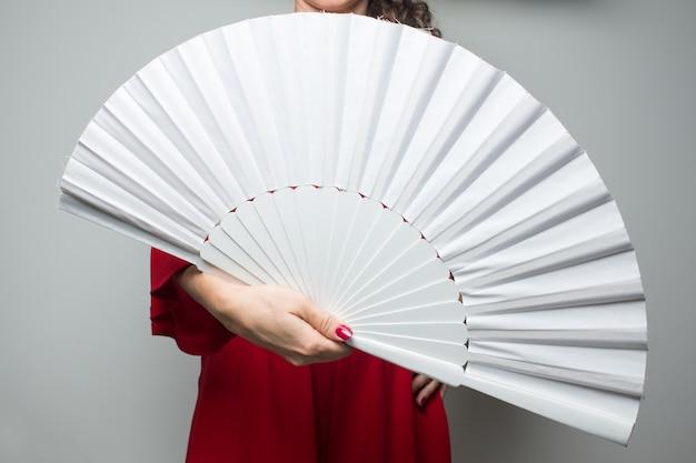 Femme en robe rouge en agitant un fan de flamenco de séville