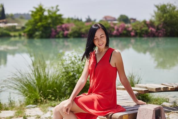Femme en robe rouge assise sur un banc