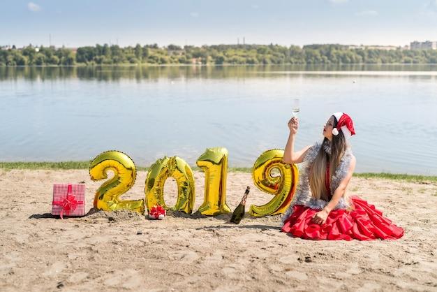 Femme en robe rouge assise près de ballons dorés sur la plage