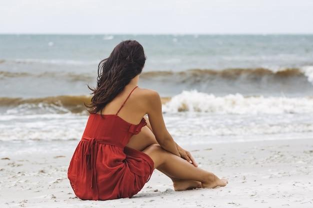 Femme en robe rouge assise sur le sable par temps froid et venteux