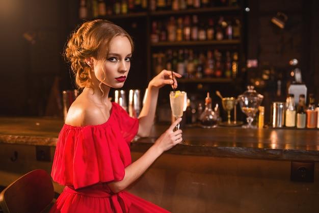 Femme en robe rouge boit un cocktail au comptoir du bar