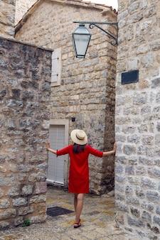Femme en robe rouge avec chapeau et lunettes de soleil debout dans la vieille ville