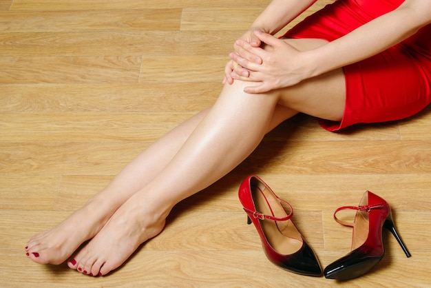 Femme en robe rouge courte est assise sur le sol sans chaussures à talons pliez vos mains sur le genou