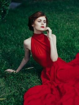Femme en robe rouge est assise sur le charme de l'herbe et le parc de style exotique de luxe.