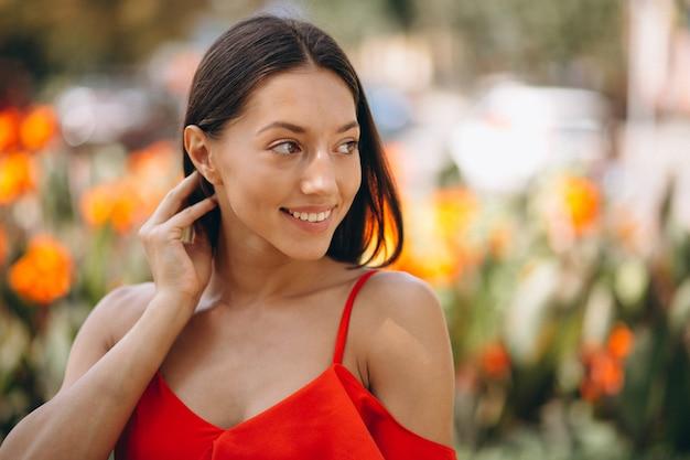 Femme en robe rouge à l'extérieur du parc