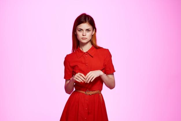 Femme en robe rouge sur fond rose studio posing model
