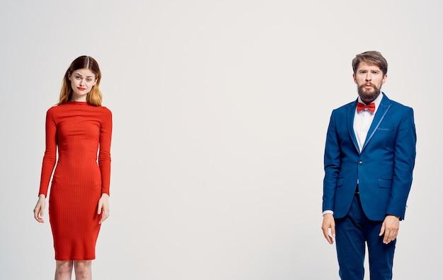 Femme en robe rouge ou homme en costume style élégant studio