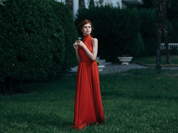 Femme en robe rouge de luxe princesse mascarade charme feuilles vertes.