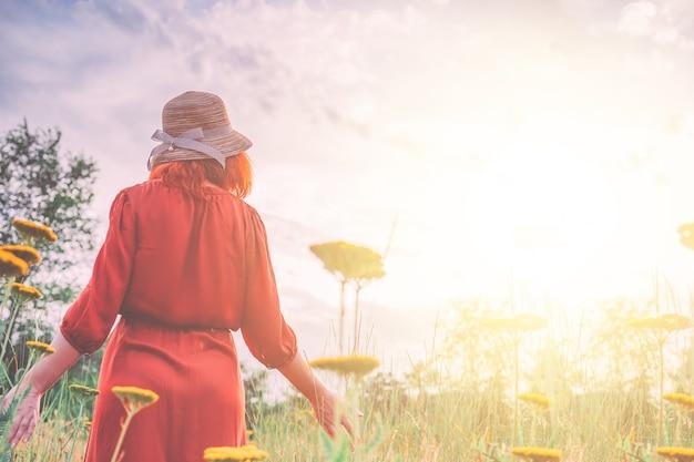 Femme en robe rouge marchant sur le terrain