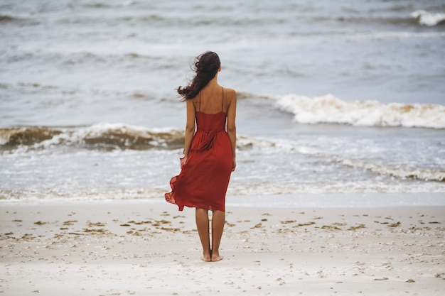 Femme en robe rouge sur la plage par temps froid et venteux