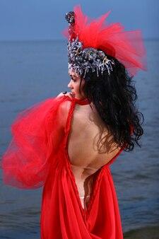 Femme en robe rouge à la plage