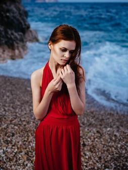 Femme en robe rouge posant rive roches océan nature. photo de haute qualité