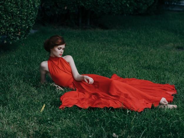 Une femme en robe rouge se trouve sur le modèle de look attrayant glamour de l'herbe. photo de haute qualité