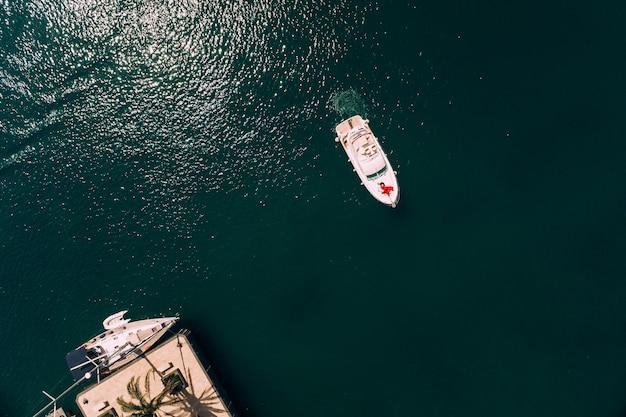 Femme en robe rouge se trouve sur la proue d'un yacht à moteur blanc naviguant vers la jetée vue d'en haut