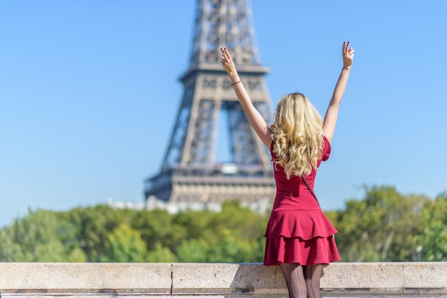 Femme en robe rouge à la tour eiffel en france