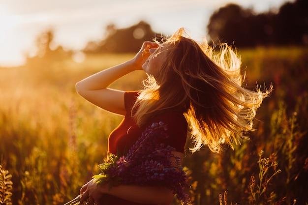 Femme en robe rouge tourbillonne dans les rayons du soleil du soir