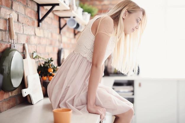 Femme avec robe s'asseoir sur la cuisine