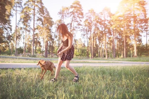 Femme en robe s'exécute avec un chien ludique dans le parc. marcher et jouer avec un chien dans les bois.