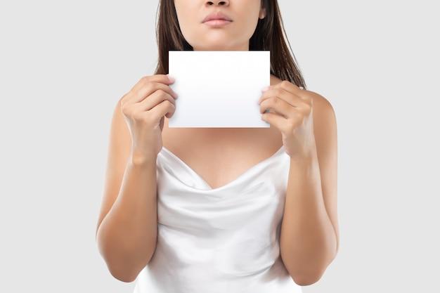 Une femme en robe de satin blanc tenant un papier blanc blanc contre un gris clair