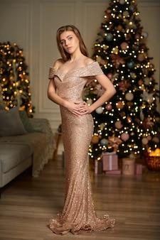 Femme en robe de soirée sur l'arbre de noël