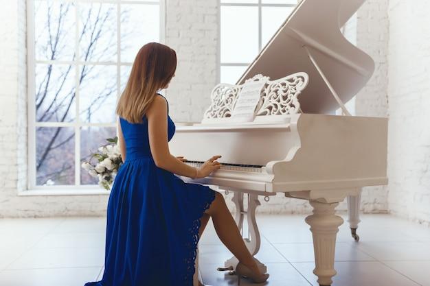 Femme en robe de soirée bleue jouant sur un piano blanc