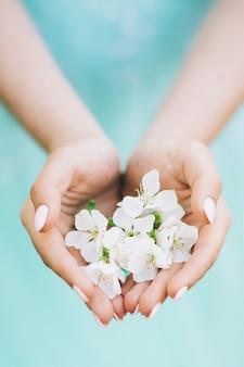 Femme en robe turquoise montrant des fleurs blanches
