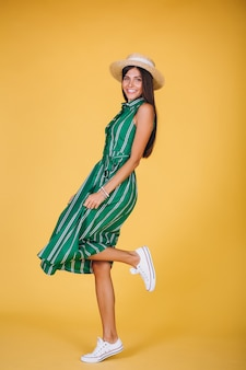 Femme en robe verte et chapeau sur fond jaune