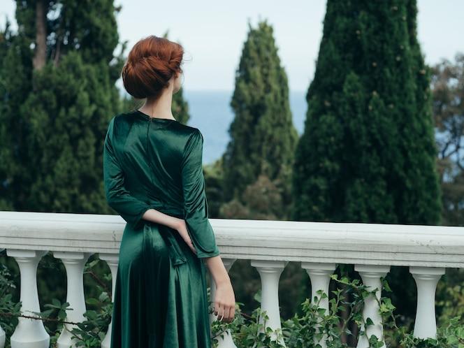 Femme en robe verte dans la promenade romantique de luxe du parc
