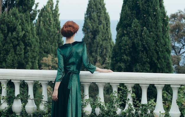 Femme en robe verte à l'extérieur mascarade beauté romance nature. photo de haute qualité