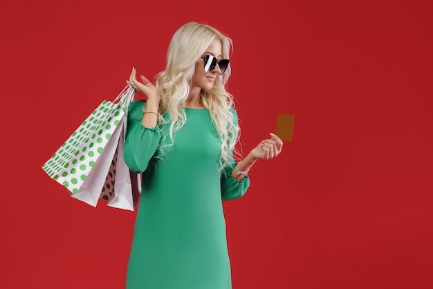 Femme en robe verte tenant des paquets et une carte de crédit. vente shopping de noël