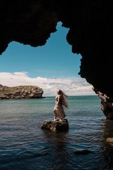 Une femme sur un rocher regardant au loin contre la mer