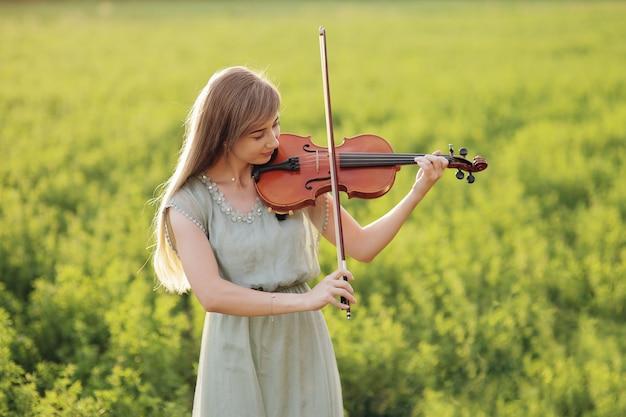 Femme romantique aux cheveux lâches jouant du violon. lumière du coucher du soleil dans la nature. formation de violon