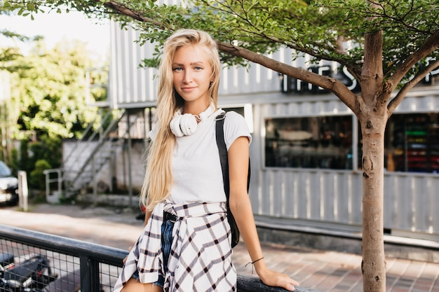 Femme romantique aux longs cheveux blonds posant avec l'expression du visage intéressé.