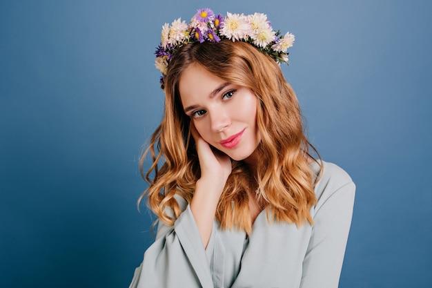 Femme romantique aux yeux bleus avec des fleurs dans les cheveux posant sur un mur sombre