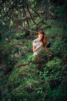 Femme romantique et belle se réveillant dans la forêt de conte de fées