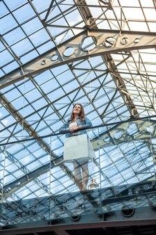 Femme romantique debout sur balcon à la gare avec plafond de verre